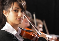 Close-up photo of violinist in orchestra