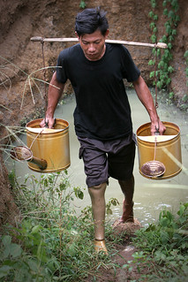 Puth Sothe, ex-soldier and landmine victim, from Chrok Porn in Cambodia, is able to plant his own vegetables and carry water from the spring because of the prosthetic leg he was given. 2005. Photo: AusAID
