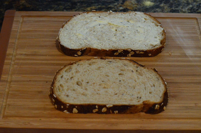 One slice of the buttered bread is flipped over.