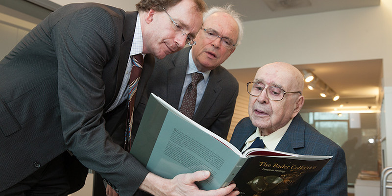 Bader Curator of European Art, David de Witt and Professor Emeritus David McTavish admire a new publication about the Bader Collection with  Alfred Bader during his visit to the Agnes Etherington Art Centre.