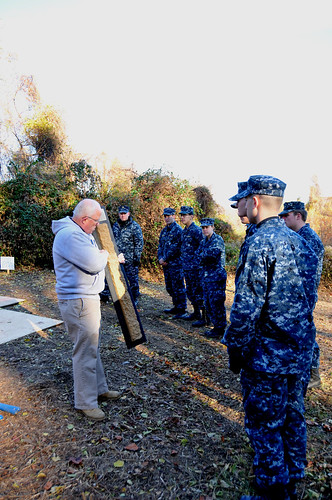 NRCS soil scientist Dean Cowherd explains a soil horizon to the midshipmen before they begin to dig. NRCS photo.