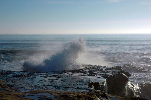 Dance of a wave spraying onto the stone coast, The Pipeline, Pacific Coast, Santa Cruz, California, USA by Wonderlane