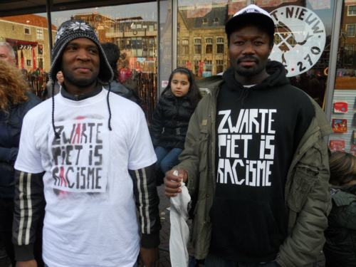 "Two black men wearing shirts that say ""zwiete piet es racisme"""