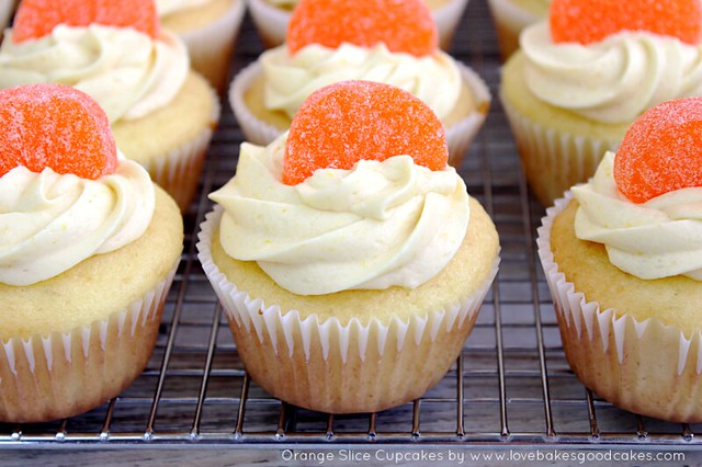 Orange Slice Cupcakes in orange bowl with an orange candies on top.