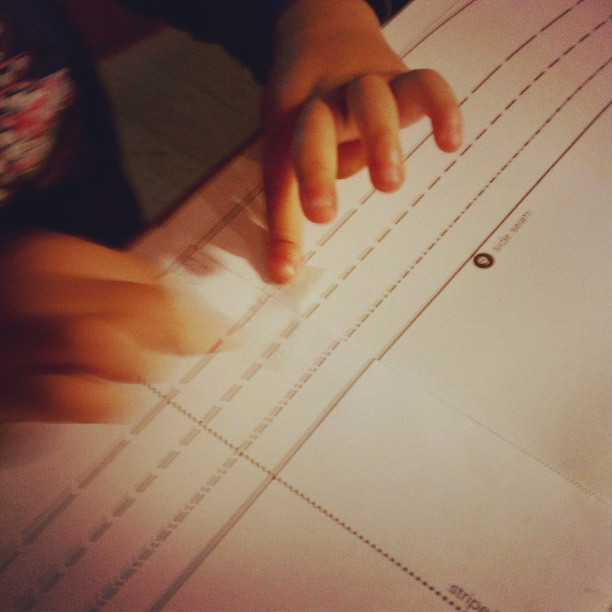 Little hands helping Mommy tape together her sewing pattern. #isew #mytoddlersews