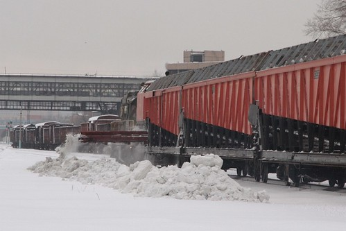 A conveyor belt at the far end of the hopper wagons discharges collected snow