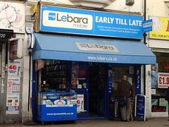 "A terraced shopfront decked out in light blue advertising for Lebara mobile. The name above the frontage is ""Early till Late"". The left-hand side of the shop is an open kiosk with mobile phone accessories hanging inside it. The right-hand side has a number of small advertisements in the window, and a person is standing in the street looking at them. An A-board outside advertises ""Cash Machine Here""."