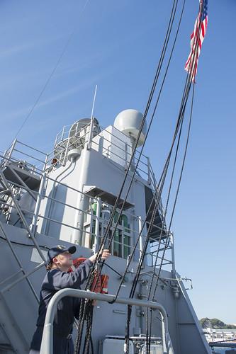 YOKOSUKA, Japan - Quartermaster 1st Class Amy Birkholz, assigned to USS Chancellorsville (CG 62), raises the national flag before the ship departs Fleet Activities Yokosuka.