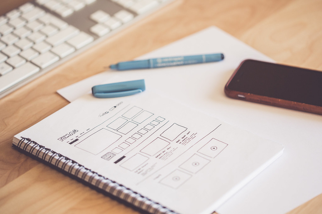 web designer sketching a wireframe layout ideas in a notebook