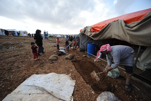 Hussein digs outside his tent near Amman to prevent flooding