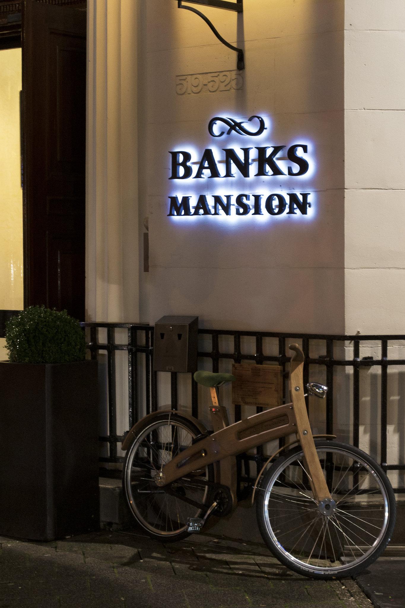 """Saving Mr Banks (auf dem Rad) [Bildbeschreibung: Ein Fahrrad mit einem Holzrahmen lehnt an einen schwarz lackierten Metallzaun an einem weiß getünchten Haus. Der Bildausschnitt zeigt nur das Rad und einen Teil der links daneben befindlichen Eingangstür des Hotels. Über dem Rad steht in weiß hinterleuchteten schwarzen Versalien """"BANKS MANSION"""".]"""