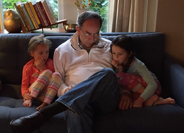 papa reading to the girls (a picture book on his iPAD :)