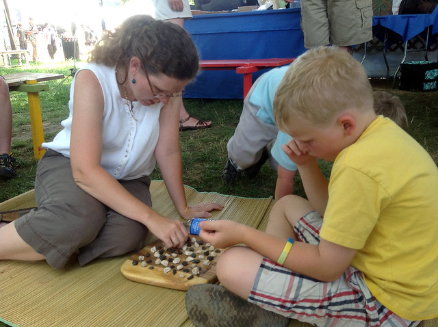 <p>Smithsonian Folklife Festival visitors try their hand at konane (Hawaiian checkers).</p>