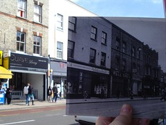 A black-and-white photo held up against a modern street scene, with edges of buildings and pavement lined up.  The modern scene shows a hairdressers called Suave Living and part of a shop called Flair.  The older photo shows shopfronts for John Hawkins & Sons Ltd, Walltones, and Express Dairies.