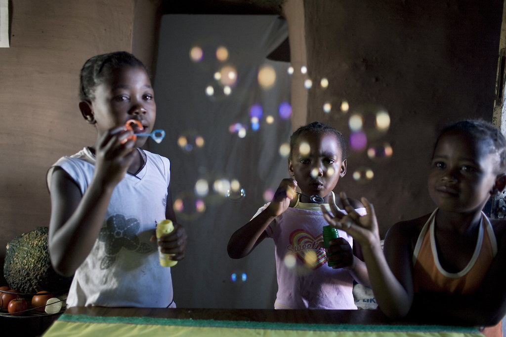 Young girls blow soap bubbles in a child headed family in Makgolokweng, Qwa Qwa, Free State, South Africa
