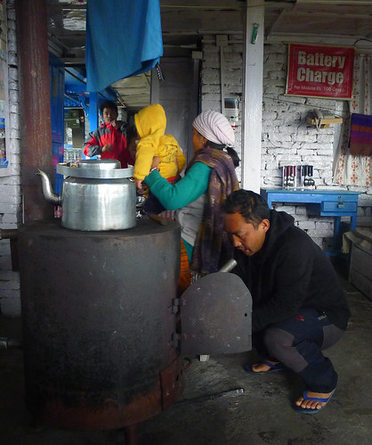 Teahouse owner warming up the stove inside the dining hall