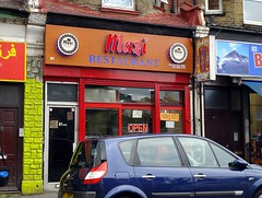 "A small terraced shopfront partly obscured by a parked car.  A door on the left of the façade is labelled ""81 A B C"".  The rest of the frontage is fully-glazed, including the shop door on the right.  Above the frontage are the words ""Mazi Restaurant"" in red and blue letters on a light brown background."