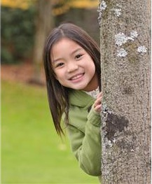 Little girl behind tree smiling