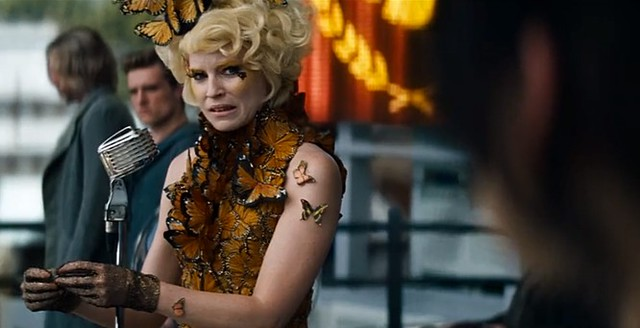 Effie Trinket, wearing a dress made of butterflys, seems upset while applauding in front of a microphone