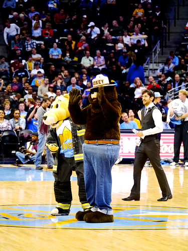 Smokey waves to the crowd at the pre-season opener with Nuggets mascot Rocky at center court. (U.S. Forest Service/Todd Riecks)