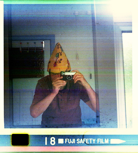 reflected self-portrait with Kodak Instamatic 233 camera and narrow yellow hat by pho-Tony