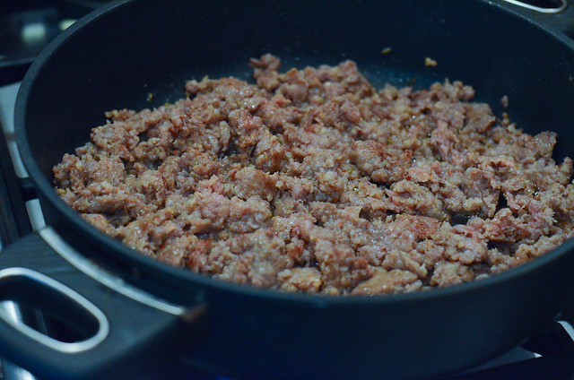 A pan filled with cooked, crumbled Italian sausage.