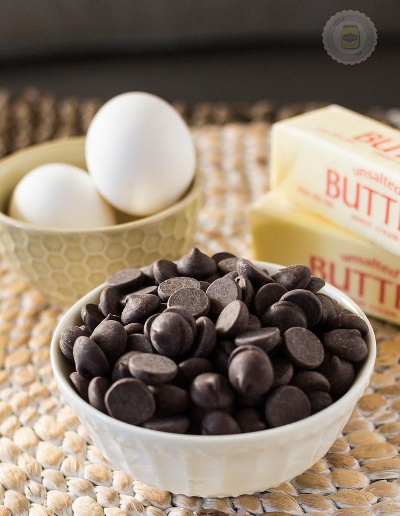 Chocolate Chips in a white bowl with sticks of butter and two white eggs in the background