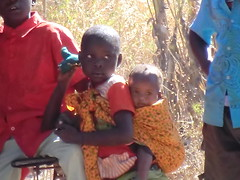 Zambia. Aldea entre Kasama y Mporokoso. Niña cargando con un bebé a la espalda