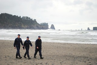 Senior Chief Petty Officer Kevin J. Ziegler, officer in charge of Coast Guard Station Quillayute River in La Push, Wash., leads Petty Officer 2nd Class James P. Thrall (middle) and Petty Officer 2nd Class Zachary T. Rowan (left) down the beach before awarding them their surfmen checks during a ceremony held in La Push, March 19, 2014. The beach walk is a surfman tradition originally started by the U.S. Life Saving Service. Senior Chief Petty Officer Kevin J. Ziegler, officer in charge of Coast Guard Station Quillayute River in La Push, Wash., leads Petty Officer 2nd Class James P. Thrall (middle) and Petty Officer 2nd Class Zachary T. Rowan (left) down the beach before awarding them their surfmen checks during a ceremony held in La Push, March 19, 2014.  The beach walk is a surfman tradition originally started by the U.S. Life Saving Service.  U.S. Coast Guard photo courtesy of Coast Guard Station Quillayute River.
