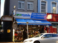 A small grocery shop with open boxes at the front holding vegetables such as yams, plantains, and chillies.  There is a blue canopy above this with the word 'Lycamobile' written on it in white and the tagline 'The UK's favourite SIM for low Cost International & National calls'.  A sign above the canopy is divided in half with a diagonal line; to the left is the word 'Lycamobile' in green and blue on a white background with the tagline 'Call the world for less' and to the right are the words 'Euro Fruiterer's [sic] / Specialist's [sic] in European Continental exoctic [sic] fruits & vegetables / 020 8288 1615' and the number '31' in white on a blue background.
