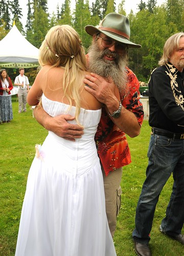 Well wishes! Jessie in her white wedding dress hugs an Alaskan friend, hat & beard, tent, reception line, Wedding of Jessie and Chris, outside, Fairbanks, Alaska, USA by Wonderlane
