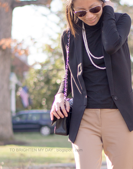 black turtleneck, black sleeveless vest, camel pants
