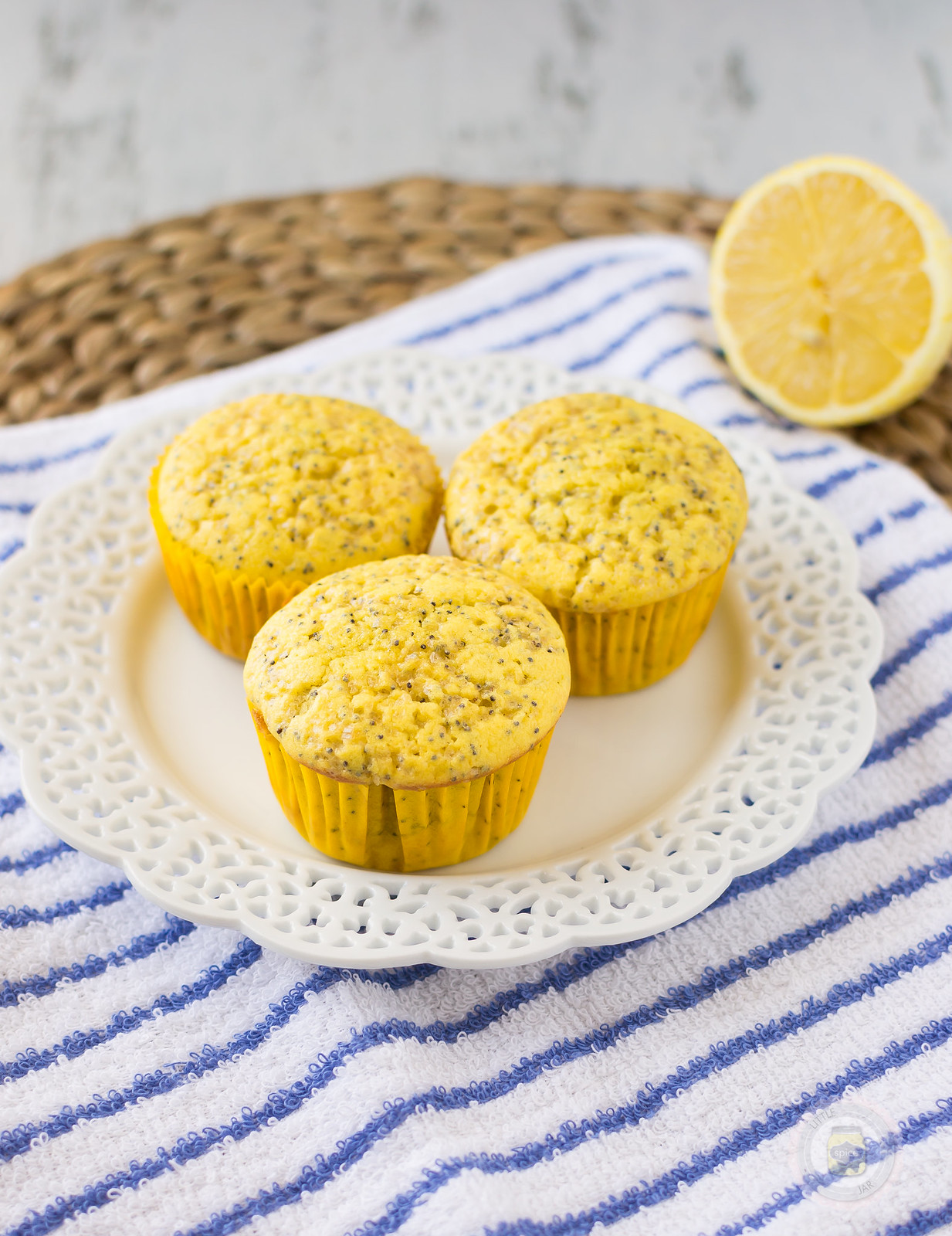 three lemon poppy seed muffins on doily plate on striped hand towel