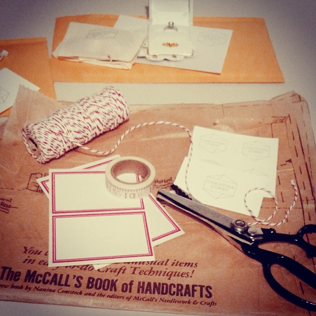 Packaging up sales with a few of my favourite things - washi tape, pinking shears, vintage sewing pattern tissue paper, red and white string, and vintage style jam labels for the bubble mailers. :) #whocanresistbrownpaperandstring