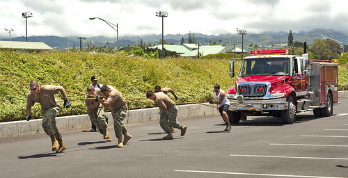<p>U.S. Sailors assigned to Joint Base Pearl Harbor-Hickam, Hawaii, compete in a firetruck pull during a fitness and health fair outside a fitness center at the base in Oahu, Hawaii, May 15, 2013. U.S. Service members, Department of Defense civilians and contractors participated in the event, which included the 200-foot firetruck pull by six-person teams. (DoD photo by Mass Communication Specialist 3rd Class Diana Quinlan, U.S. Navy/Released)</p>