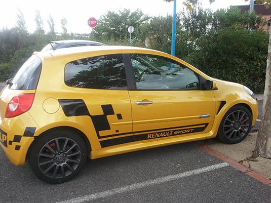 Pose des stickers sur une voiture de type clio Sport jaune.