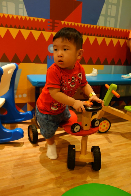 Jerome getting on a wooden tricycle in fidgets