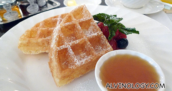 Belgian waffle served with honey and berries