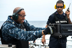Chief Culinary Specialist Morio Hall and Gunner's Mate 1st Class Clarence Hall take part in a gunnery exercise in the South China Sea, Aug. 11 aboard USS Freedom (LCS 1). (U.S. Navy photo by Mass Communication Specialist 3rd Class Karolina A. Oseguera)