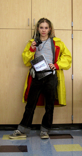 A girl dresses up as Harriet the Spy in a yellow raincoat.