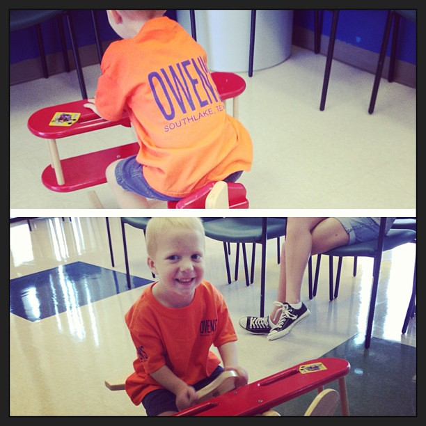 "Owen (feeling all better) gets to accompany his sisters to their well visits (they're less than thrilled to be here). He found a plane to ride, toy story is playing in the waiting room, & his orange ""Owen"" shirt is finally dry (we painted it yesterday)."