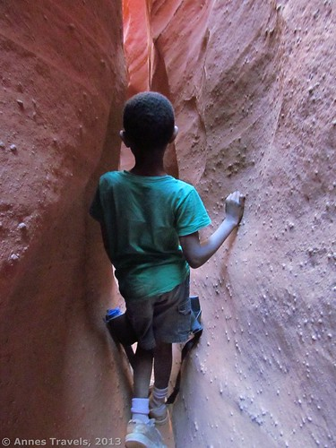A child walking through Spooky Slot, Dry Fork Slots, Grand Staircase-Escalante National Monument, Utah