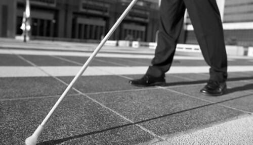 Photo of a white cane near the sidewalk