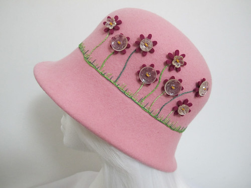 Hand blocked wool felt baby pink cloche hat featuring a floral design with hand embroidery, felt flowers and vintage buttons