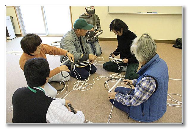 かんじき作りの講師は坂井先生.教わりながら縄を巻き付けていく.