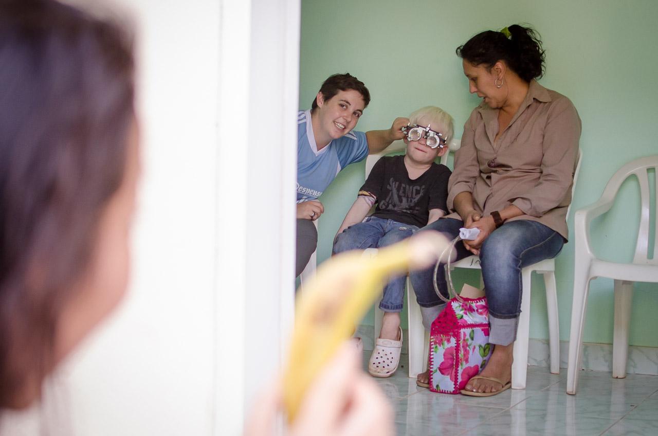 Un niño afectado por el trastorno de albinismo y al mismo tiempo con discapacidad trata de distinguir las formas de los objetos distantes con la ayuda de los marcos de ensayo. Los voluntarios procuran realizar los exámenes de la mejor manera debido a que el niño no puede comunicarse y no comprende las letras o los números. (Elton Núñez)