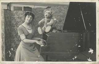 Photographic postcard of a woman, possibly actress Marjorie Neil, and toy bear at a piano