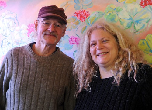 Atz Kilcher and Linda Lane, posing in front of a painting of flowers, wearing sweaters, photo by Bonnie Kilcher, 3 Sisters Cafe, mid-winter, Homer, Alaska, USA by Wonderlane