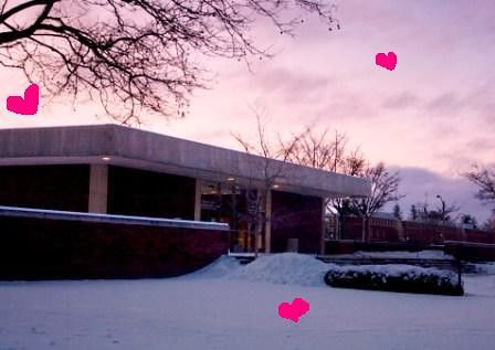 Tiny pink hearts float in front of the snowy UGL at sunset.