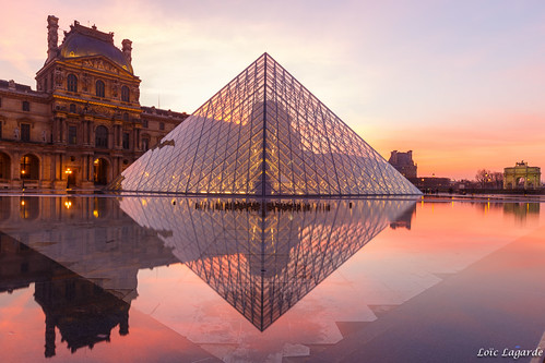 Wet reflection of Pyramide du Louvre after sunset in Paris
